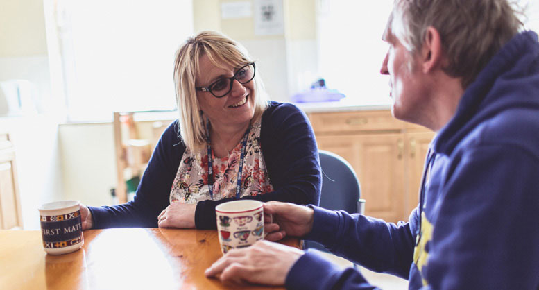 Service user having a cup of tea with smiling staff member