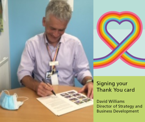 David Williams Director of Strategy and Business Development signing the staff thank you card in his office at Berrywood Hospital, Northampton