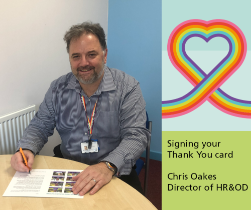 Chris Oakes Director of Human Resources and Organisational Development signing the staff thank you cards in his office at Berrywood Hospital, Northampton