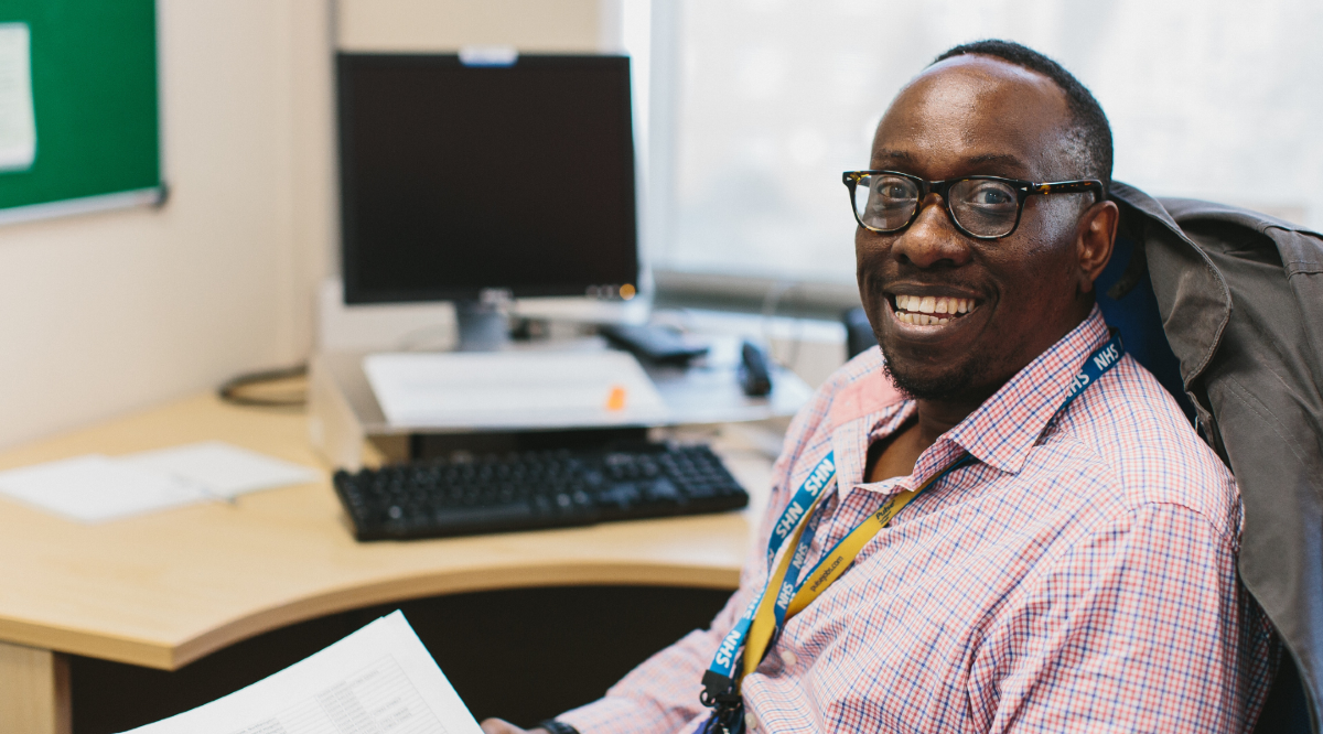 Male NHFT colleague in office wearing a shirt, smiling