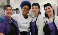 Four colleagues in uniform and aprons smiling